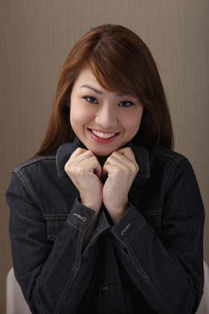Young woman smiling with hands under chin