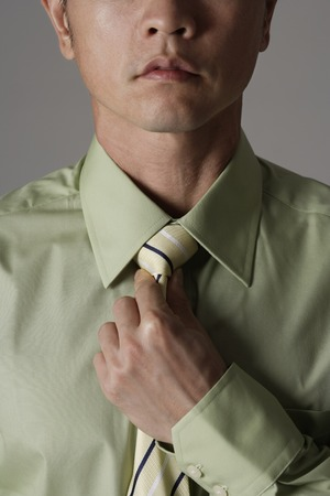 crop portrait of man tightening tie 版權商用圖片