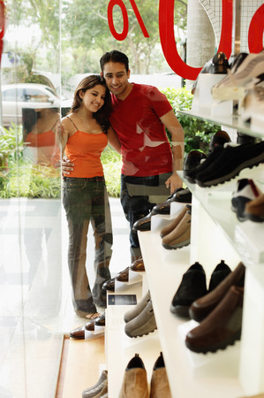 shoe shop: Couple standing outside shoe shop, looking at window display