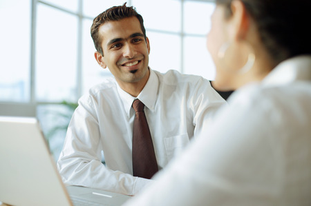 Executive smiling at person in front of him