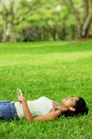 Young woman listening to music with headphones, lying on grass