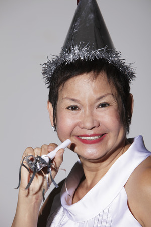 Mature Chinese woman wearing a party hat and smiling
