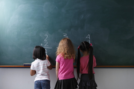 rear view of 3 young girls writing on chalk board
