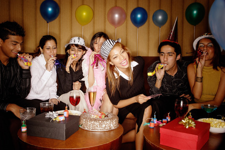 Young adults celebrating birthday, wearing party hats