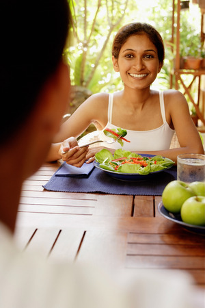 Woman at table with plate of salad, looking at man across from her LANG_EVOIMAGES