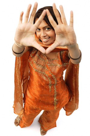 Woman in Indian clothing, holding hands up and looking at camera through them
