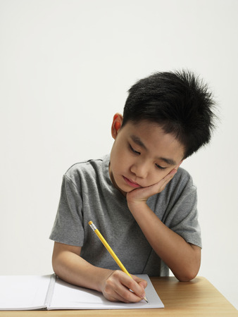 tiredness: young boy working and writing LANG_EVOIMAGES