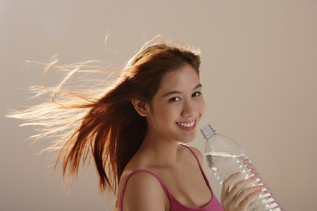 Asian girl holding bottle water with hair blowing Stock Photo