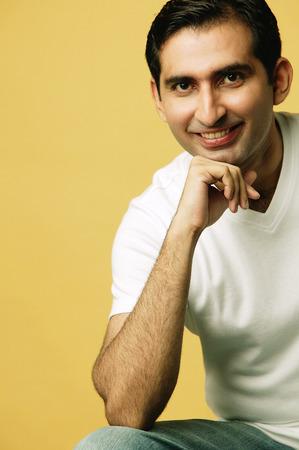 Man smiling at camera, hand on chin