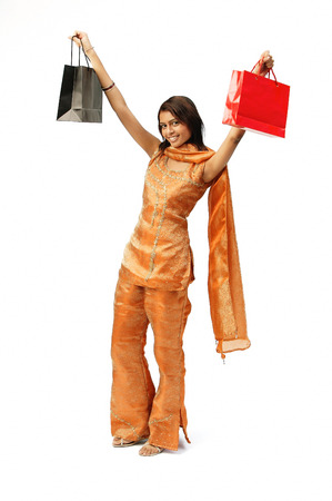 Woman in Indian clothing, arms outstretched, carrying shopping bags