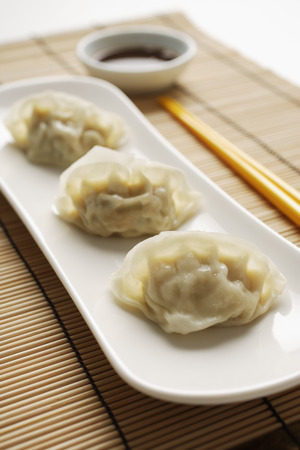 3 steamed gyoza dumplings placed on white plate with sauce on the side