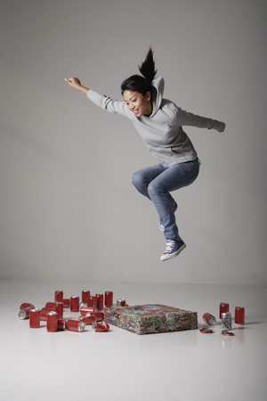 Young Asian woman jumping on cans