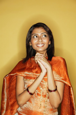 kameez: Woman in Indian clothing, hands clasped, smiling