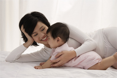 Woman lying on bed with baby girl Stock Photo