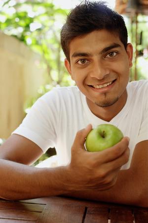 Man holding apple, looking at camera