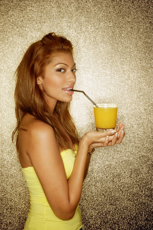 Young woman sipping drink with straw, looking at camera