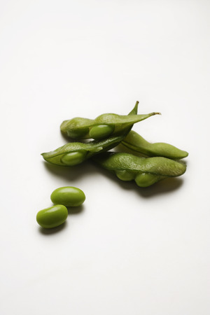 multiple green edamame beans with pea pod broken Stock Photo