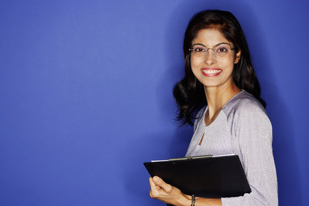 librarians: Woman looking at camera, carrying clipboard LANG_EVOIMAGES