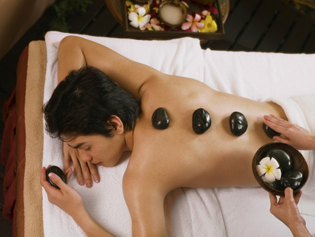 hot stones: young man getting a hot stones massage