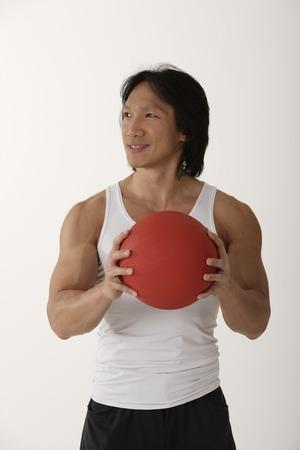 Chinese man holding medicine ball