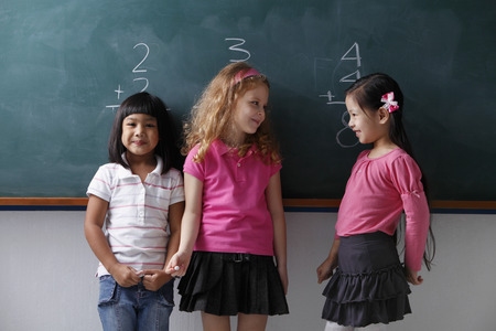 three young girls standing in front of a chalk board, smiling at each other