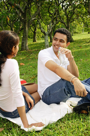 facing each other: Couple sitting on picnic blanket, facing each other, man drinking from water bottle LANG_EVOIMAGES
