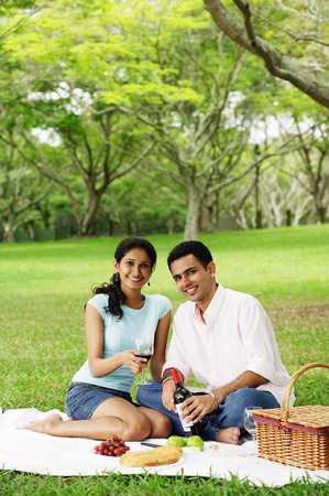 Couple in park, having a picnic, looking at camera