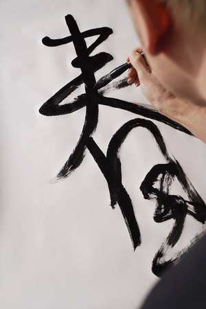 Man writing Chinese calligraphy, character for Spring