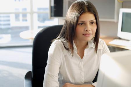 female executive: Female executive facing computer, portrait LANG_EVOIMAGES