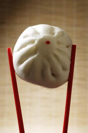 chop sticks: close up of red chop sticks holding steamed bun
