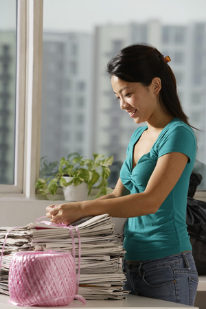 Young Asian woman recycling newspapers