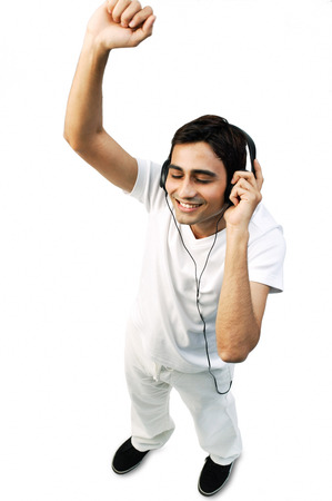 puños cerrados: Young man listening to headphones, eyes closed, arms raised LANG_EVOIMAGES