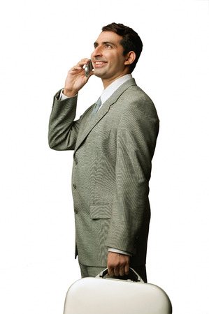 Businessman using mobile phone, carrying briefcase, smiling