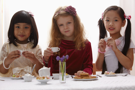 Three young girls having a tea party