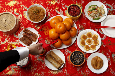 Hand reaching for red envelope (Hong Bao) on table set for Chinese New Year.