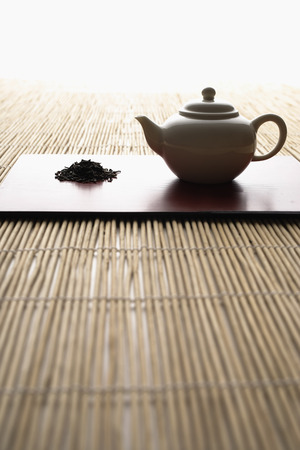three objects: tea leaves in a pile and tea pot on bamboo mat