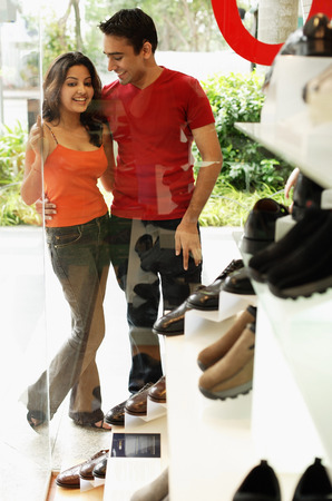 shoe shop: Young man and woman standing outside shoe shop LANG_EVOIMAGES