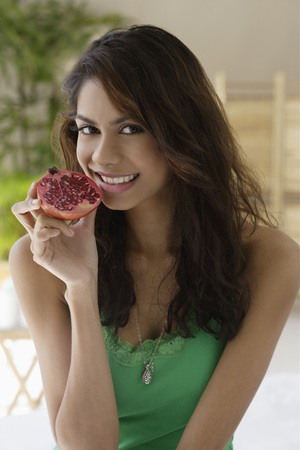only 1 person: A woman eating fruit LANG_EVOIMAGES