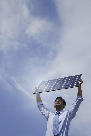 Businessman holding solar panel outside.