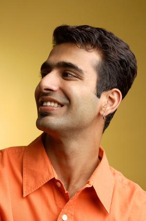 Man smiling, looking away, head shot LANG_EVOIMAGES