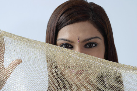 Young woman hiding behind veil