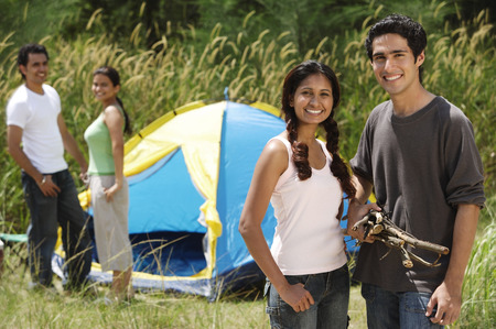 Young friends camping in the wilderness, smiling at camera Stock Photo