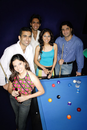 Young adults standing around pool table