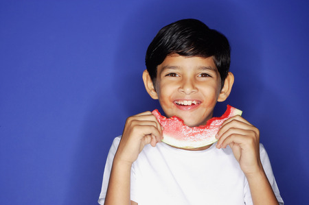 eating fruits: Boy looking at camera, holding half eaten slice of watermelon