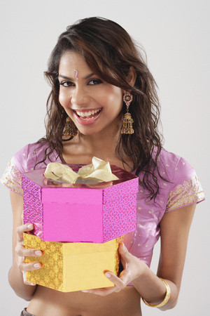 A young woman smiles at the camera as she holds gifts