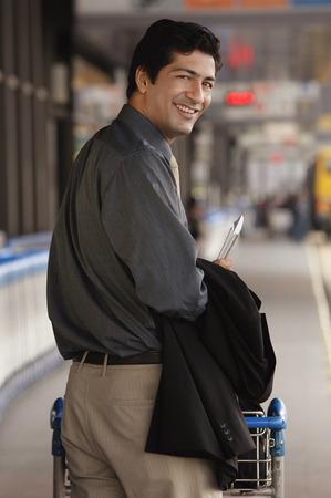 professionally: Man pushing trolley in airport, smiling at camera