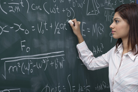 writing western: Woman working on equations on chalk board LANG_EVOIMAGES