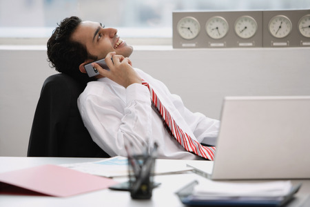 wasting away: Businessman in office, using mobile phone