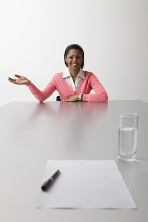 interviewed: Young woman sitting at end of table being interviewed