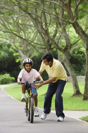 A father teaches his son to ride a bike